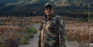 Brian Grandbois, Dene land defender, stands in camo and sunglasses on a field looking at the camera.